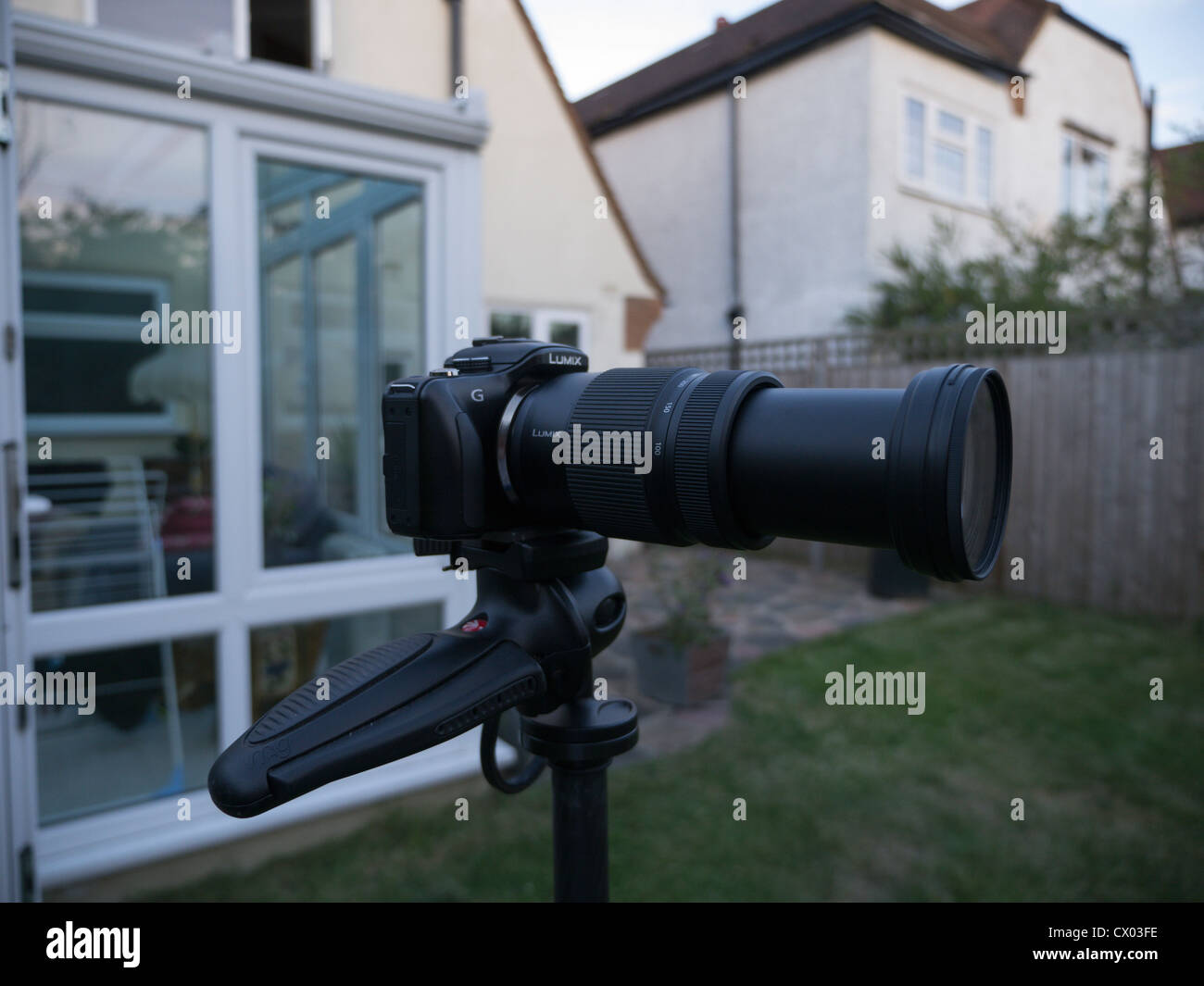 A Panasonic camera with telephoto zoom lens on a tripod in a garden. - Stock Image