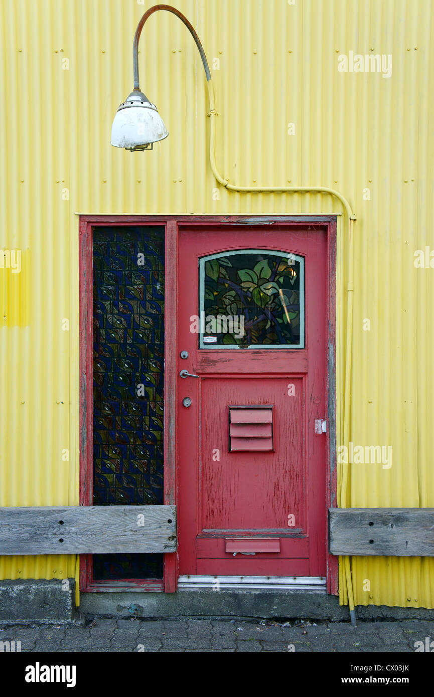 Red door and yellow building, Granville Island, Vancouver, British Columbia, Canada - Stock Image