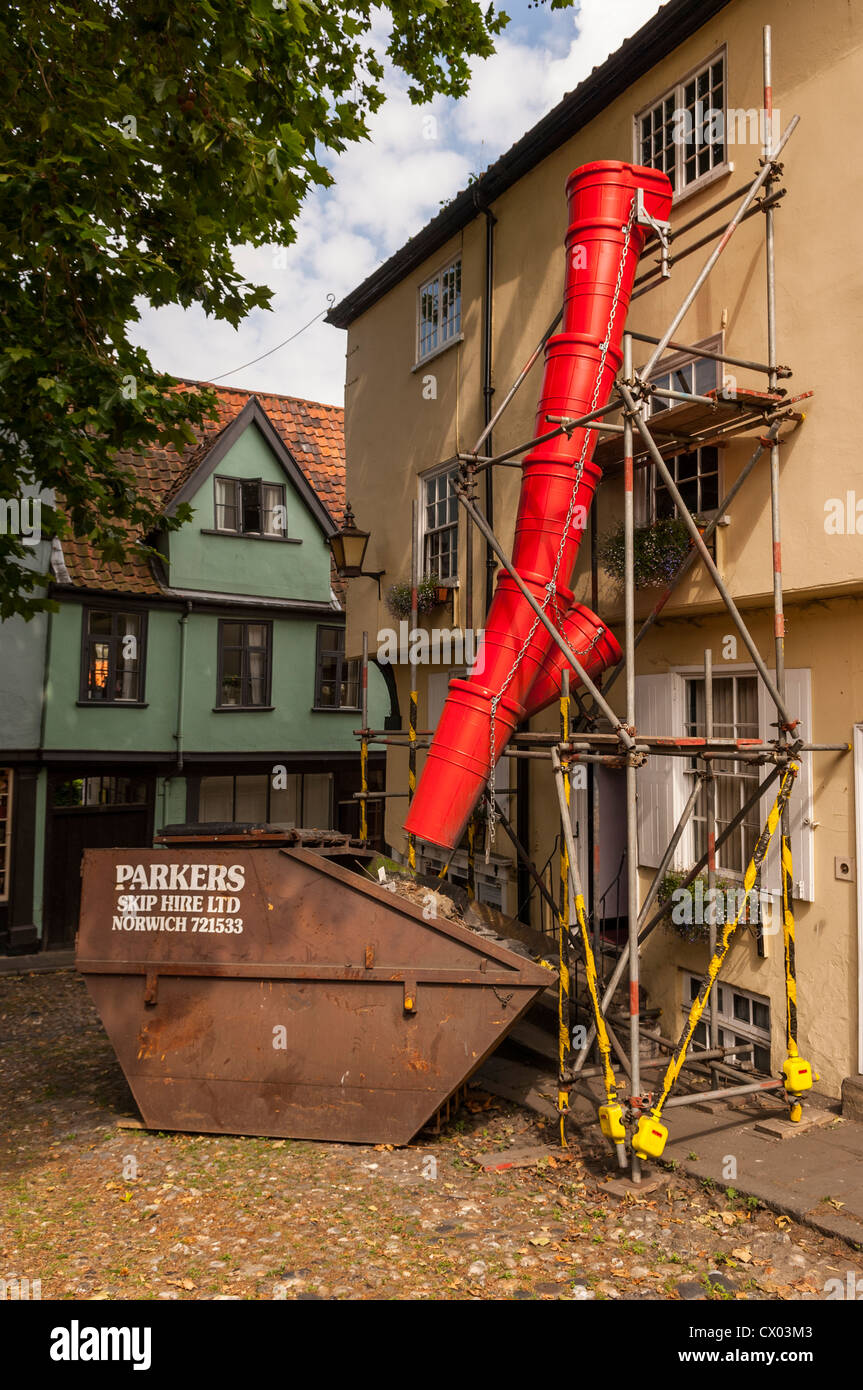 A builders rubbish chute goes into a skip in Norwich , Norfolk , England , Britain , Uk - Stock Image