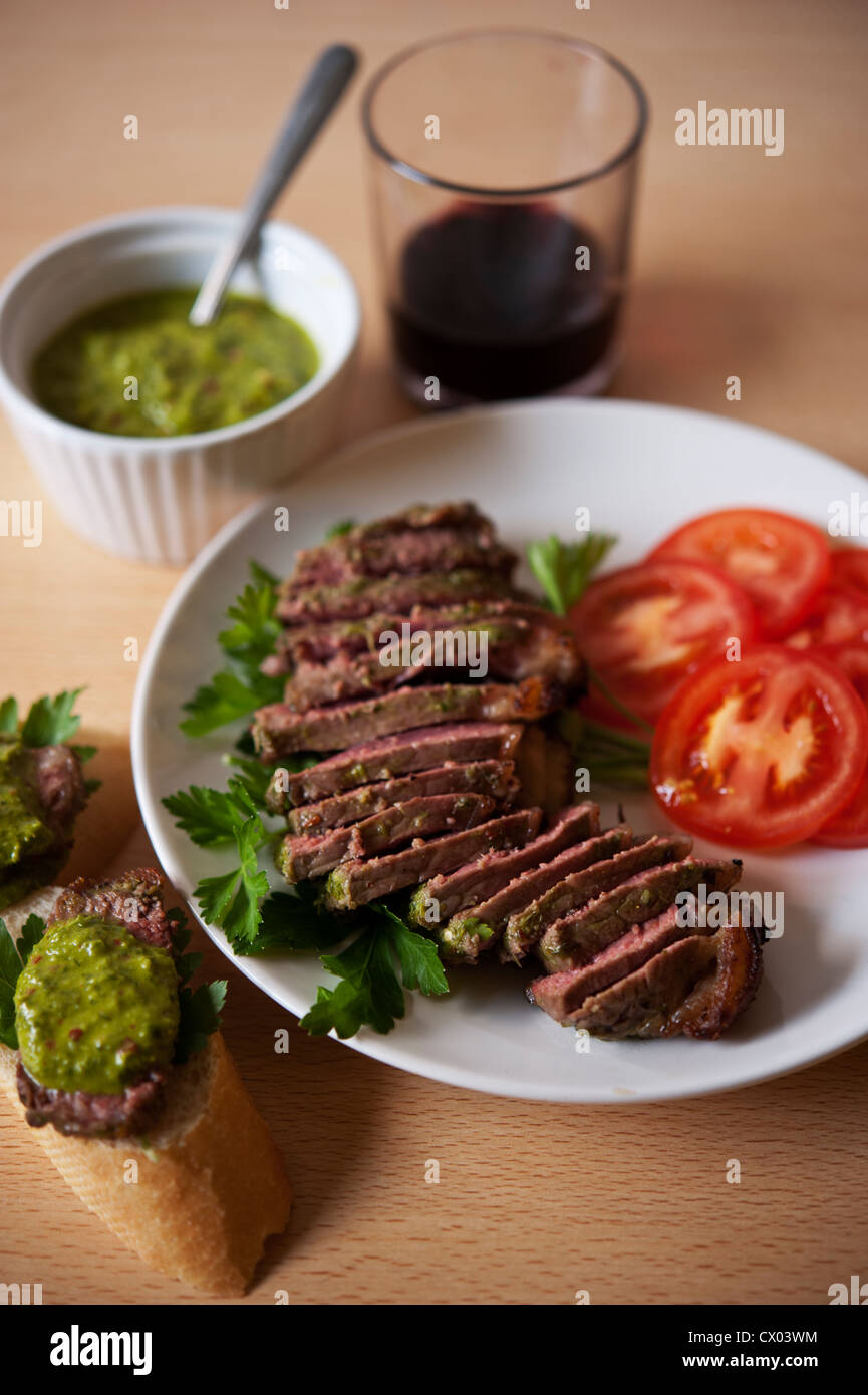 Sliced steak with chimichurri sauce. Stock Photo
