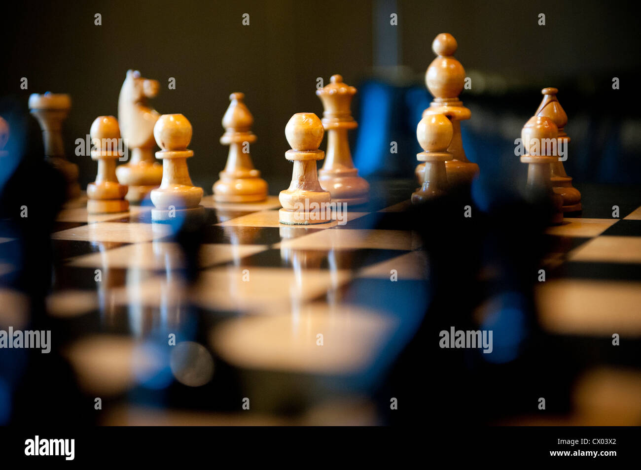 Carved wooden chess pieces on a chess board in warm light. Stock Photo