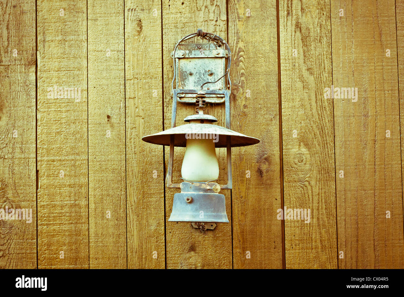 A nice vintage paraffin lamp mounted on a wooden wall - Stock Image