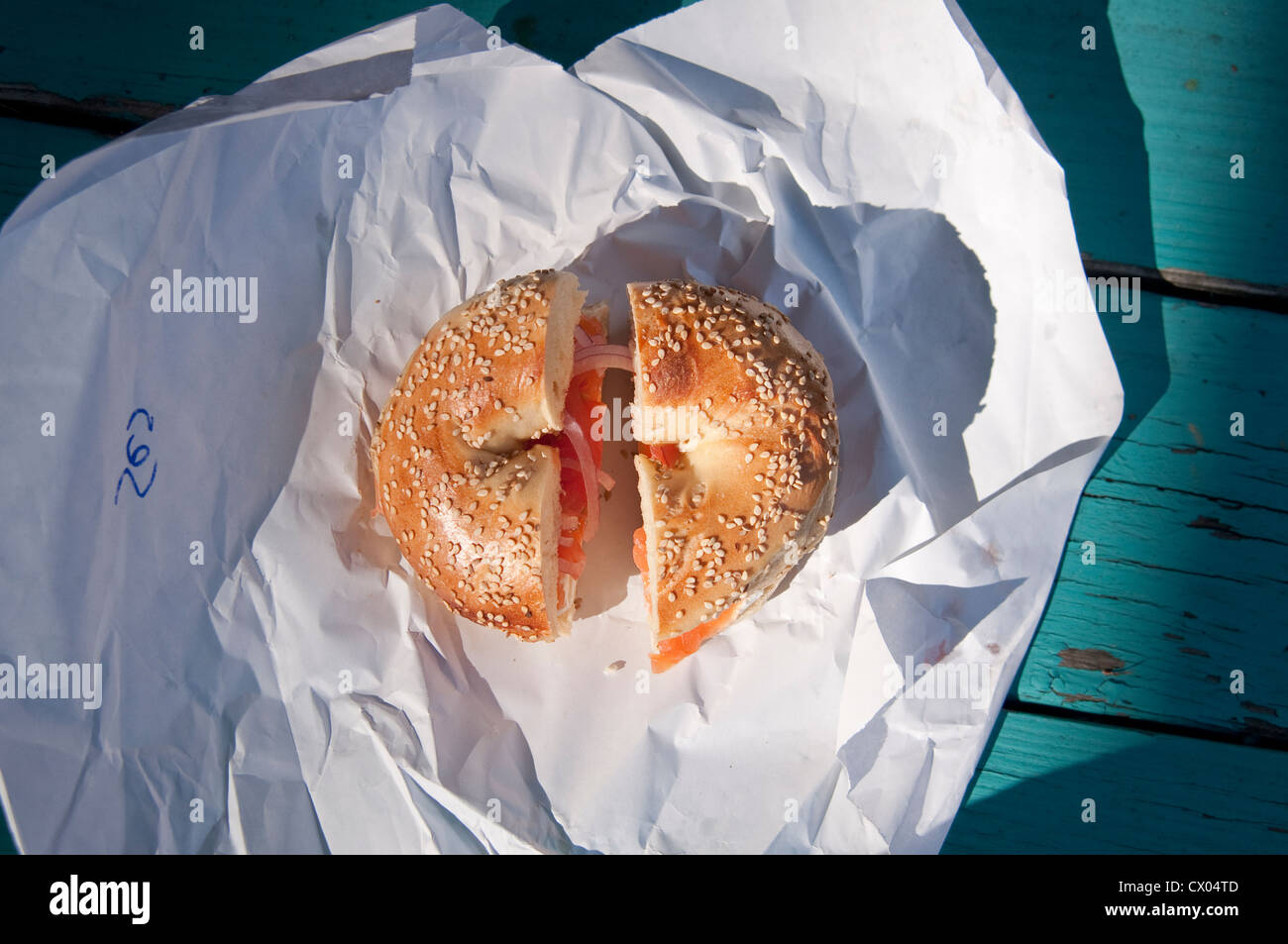 A sesame seed bagel with lox (smoked salmon), cream cheese, onion and tomato, sitting on a paper wrapper, from Spring Stock Photo