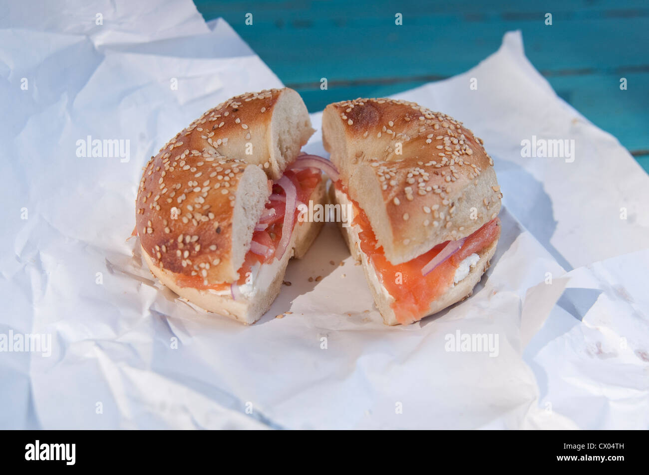 A sesame seed bagel with lox (smoked salmon), cream cheese, onion and tomato, sitting on a paper wrapper, from Spring - Stock Image
