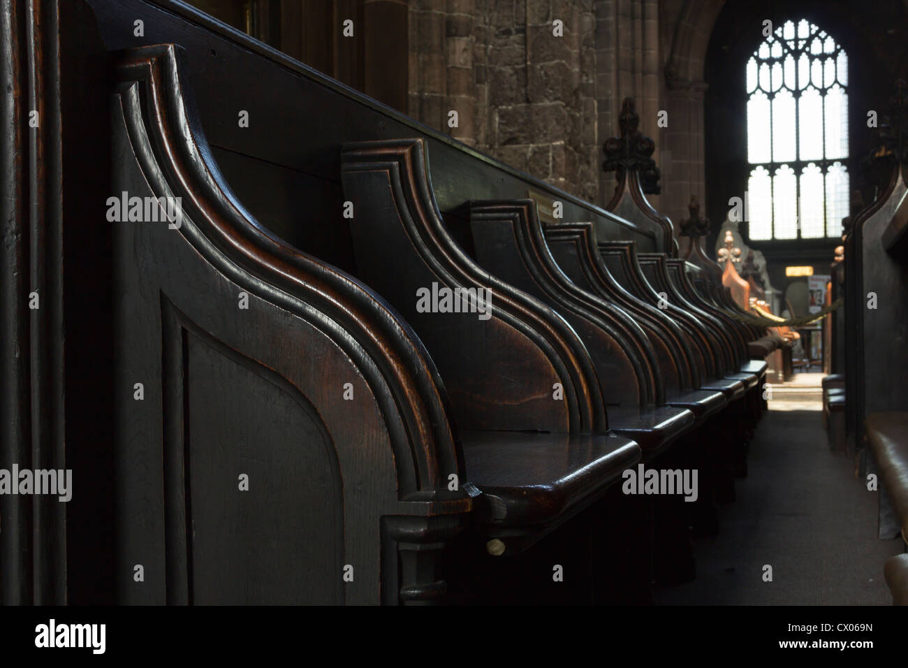 Old carved wood pew type seating at the rear of the nave of Manchester cathedral. - Stock Image