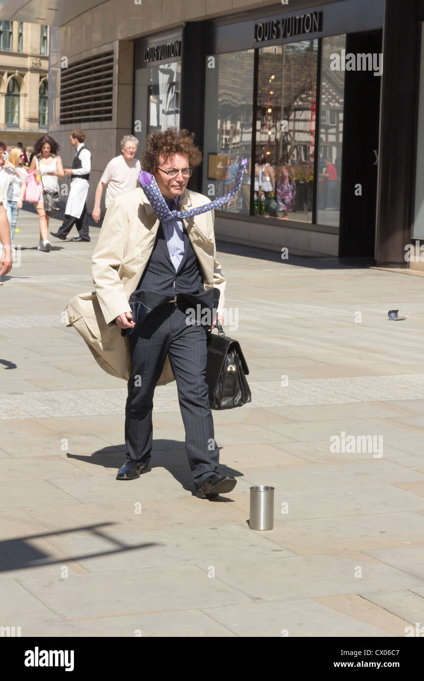 Human Statue or Living Statue street mime artist posing as a hurrying, windswept businessman in Manchester. - Stock Image