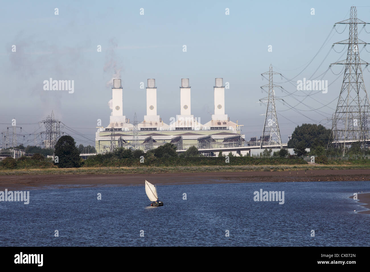 A fisherman sails an old wooden boat on the river Dee with Connah's Quay power station in the background, North - Stock Image
