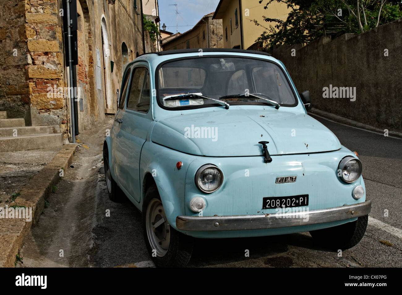 Old light blue Fiat 500 parked in street, Guardistallo Tuscany Italy