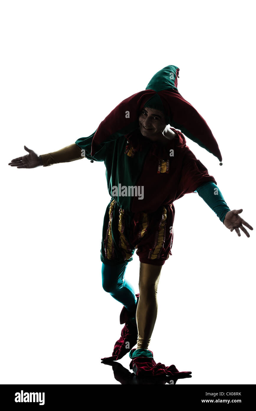 one caucasian man in jester costume saluting silhouette in studio isolated on white background - Stock Image
