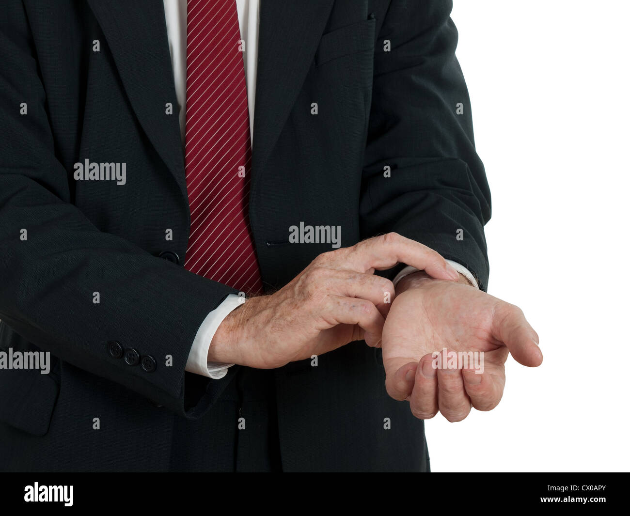 Man in business suit taking his own pulse, white background - Stock Image