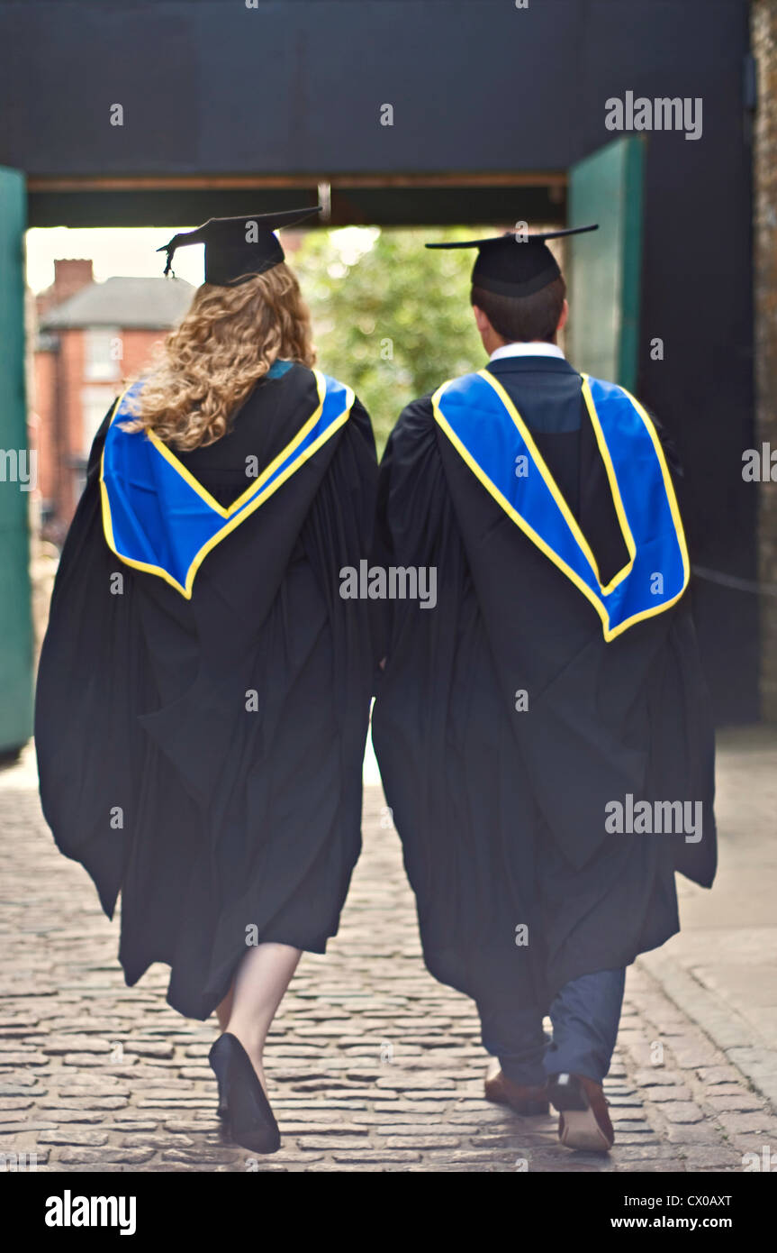 Two graduates walking away together at their graduation ceremony - Stock Image