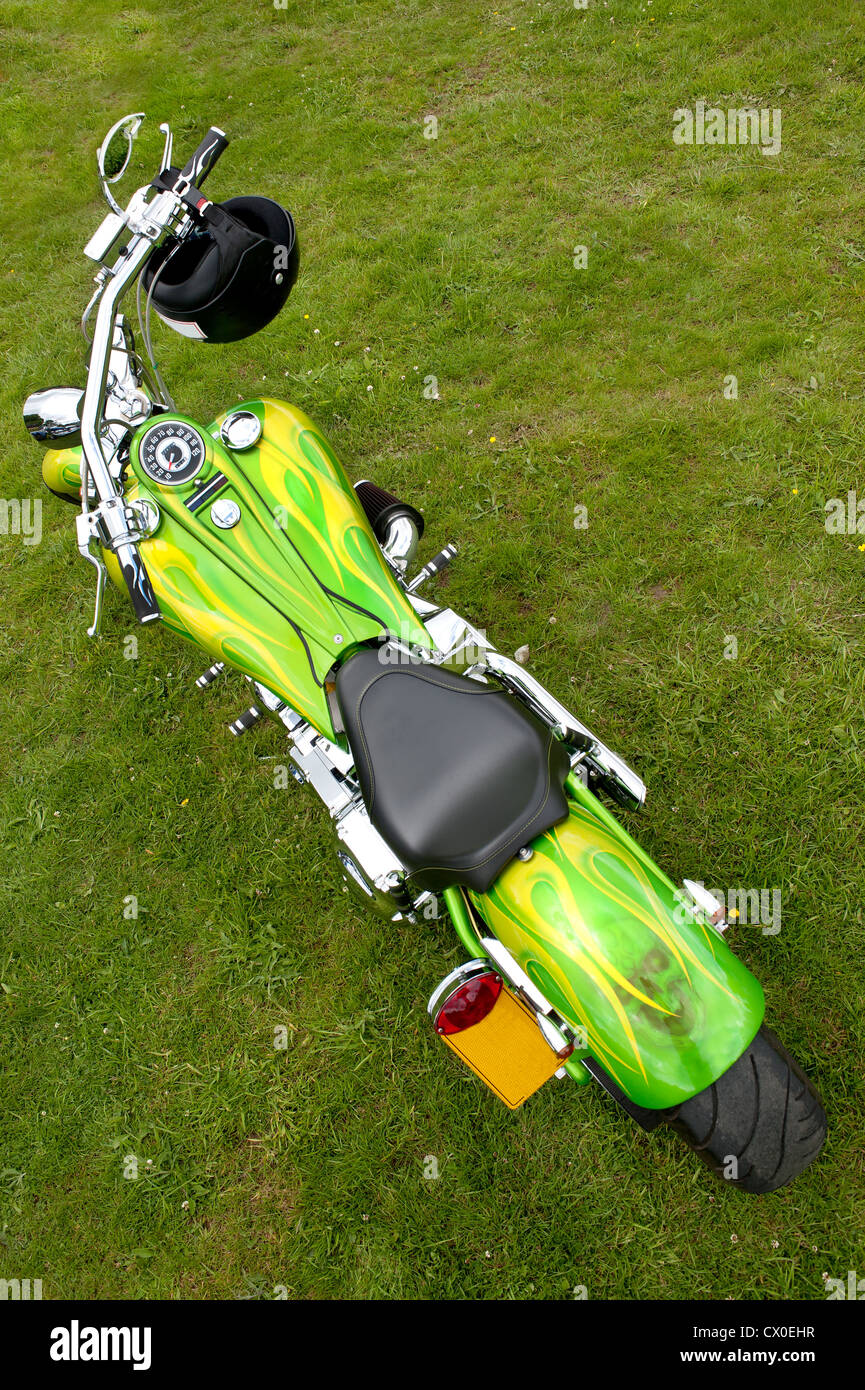 seen from above a custom painted green and yellow large customised motorbike with crash helmet - Stock Image