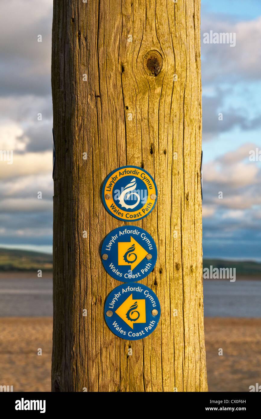 Waymarker signs for the Wales Coast Path on Aberdyfi (Aberdovey) beach (in evening light) Dyfi estuary, Gwynedd, - Stock Image