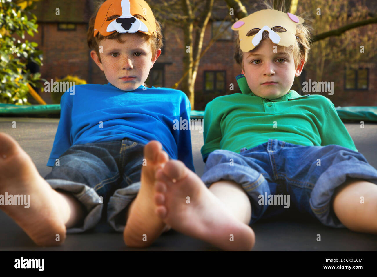 Two Boys Wearing Masks Lying on Trampoline Stock Photo