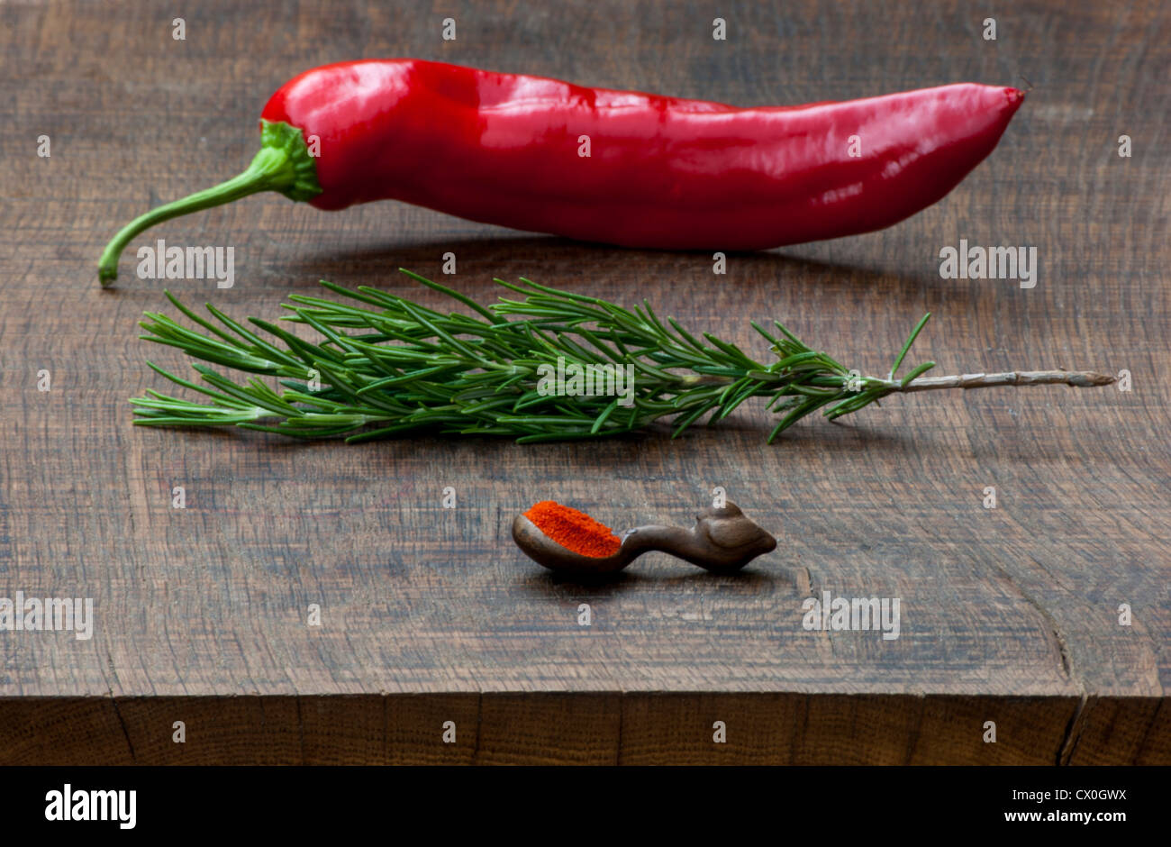 Fresh red pepper, sprig of rosemary, wooden measuring spoon of ground red pepper spice on dark, wooden chopping - Stock Image
