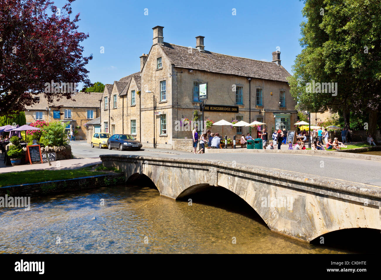 Old stone bridge over the River Windrush throught the centre of Bourton on the Water Gloucestershire England UK - Stock Image