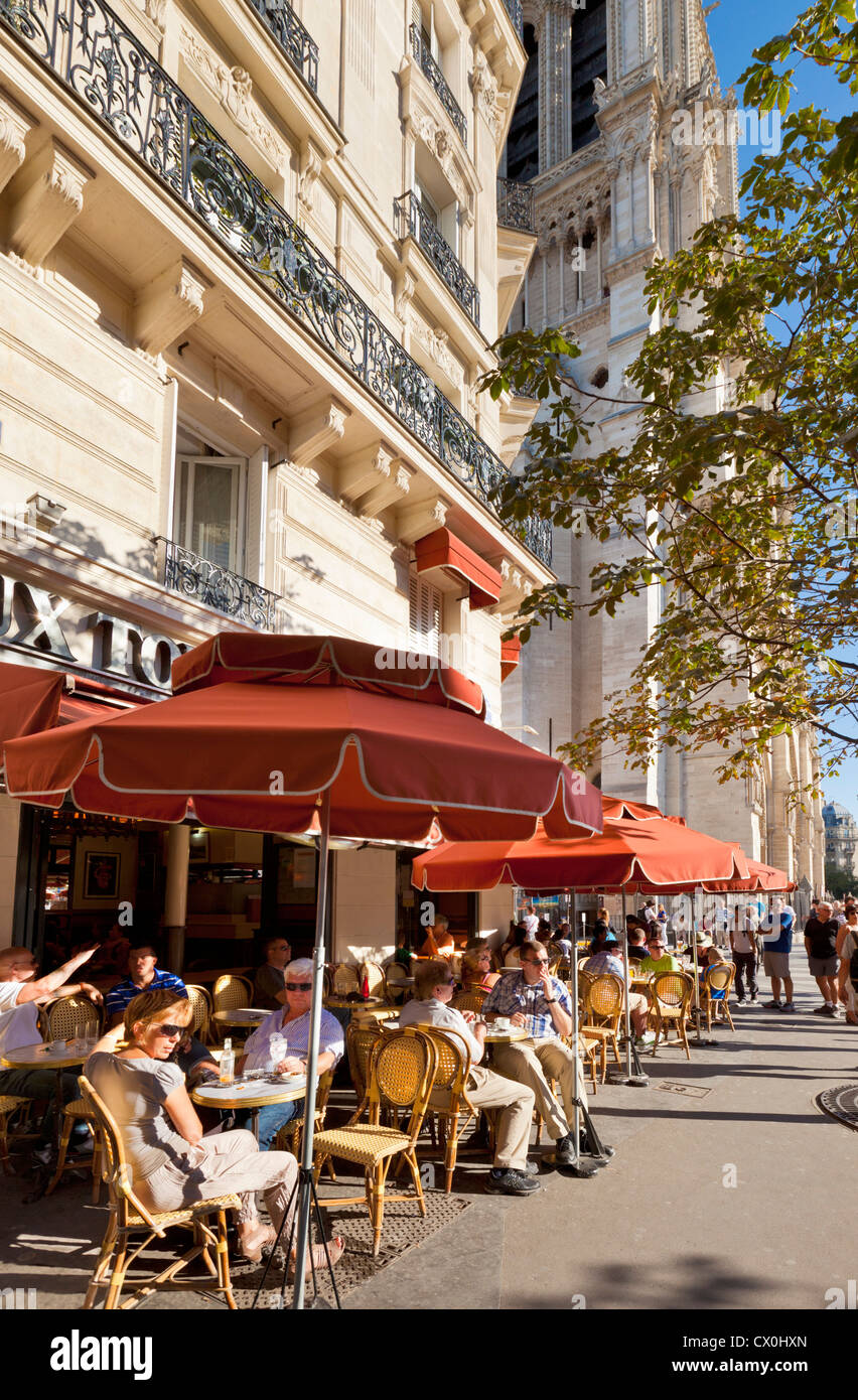 People sitting at a pavement cafe on a street avenue Paris France EU Europe - Stock Image