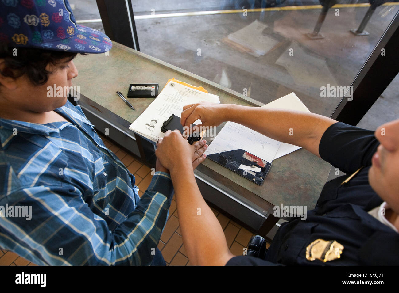 Mexican citizens wait  fill out paperwork to travel to the US. Security measures include fingerprinting by US Border Stock Photo