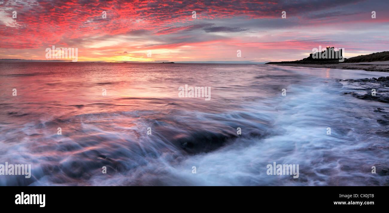 Sunrise over Bamburgh Castle on the Northumberland coast. - Stock Image