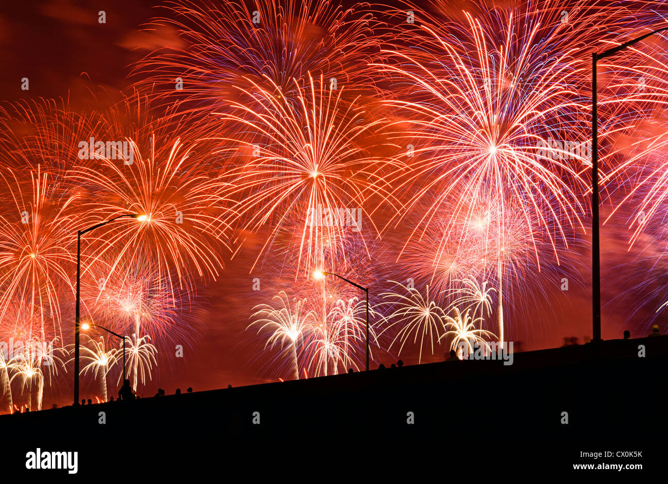 People watch Fourth of July Fireworks from elevated overpass. - Stock Image