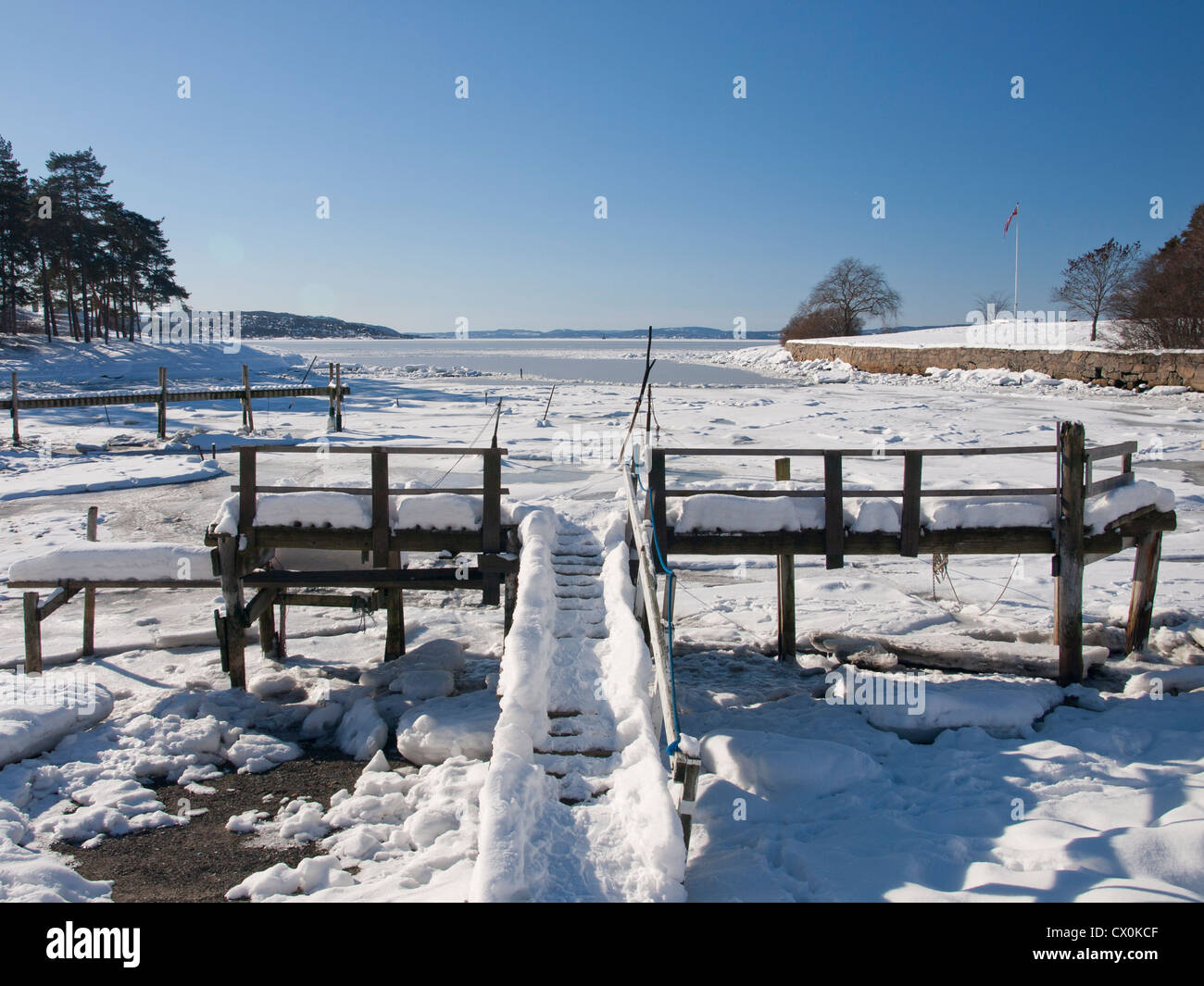 Snow covered pier at Bygdøy in Oslo Norway with view of the ice covered Oslofjord Stock Photo