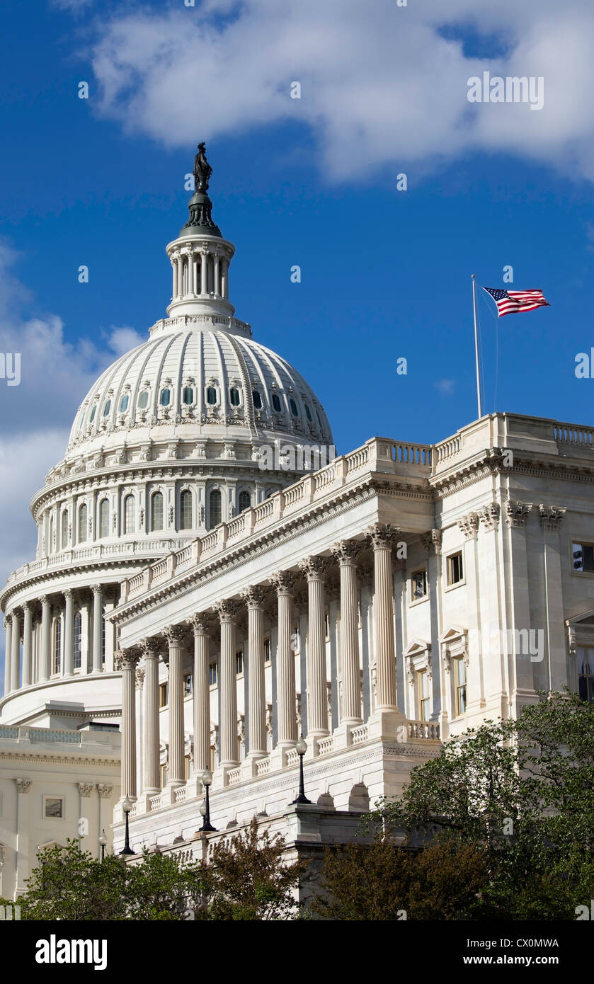The U.S. Capitol on a sunny day with American flag. View shows dome plus the wing that is home of the House of Representatives. - Stock Image