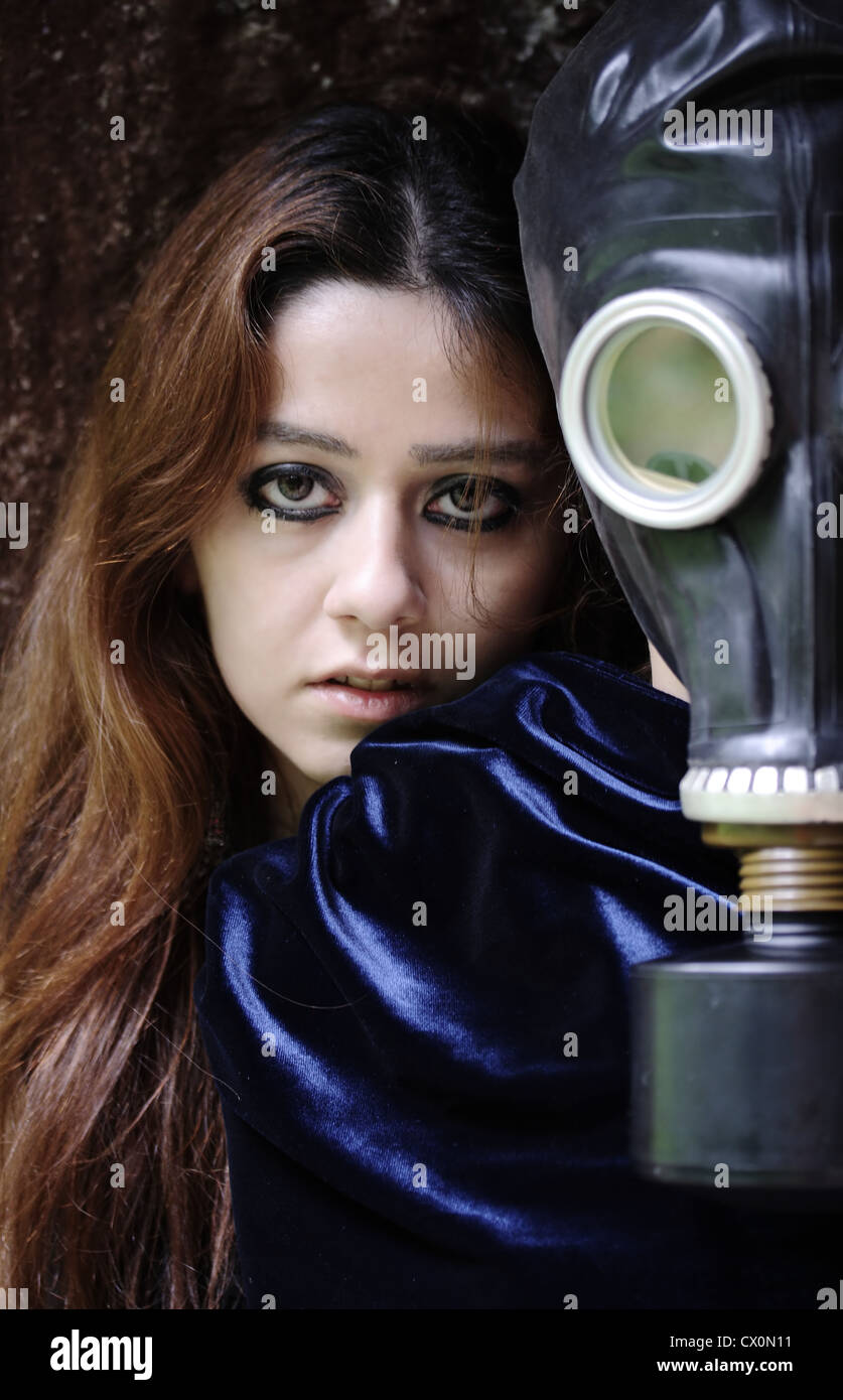 portrait of young woman and stalker with gas mask on his face - Stock Image