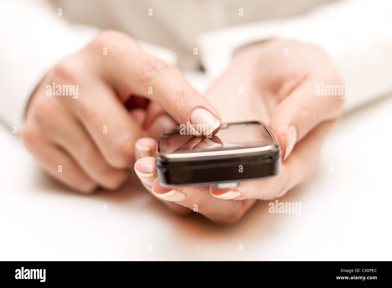Closeup of female hands using a smart phone. - Stock Image