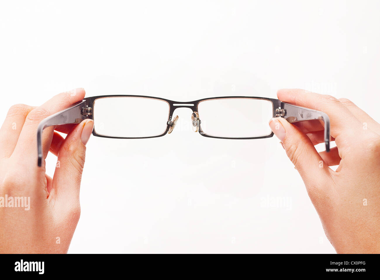 Hands holding eyeglasses on white background. - Stock Image