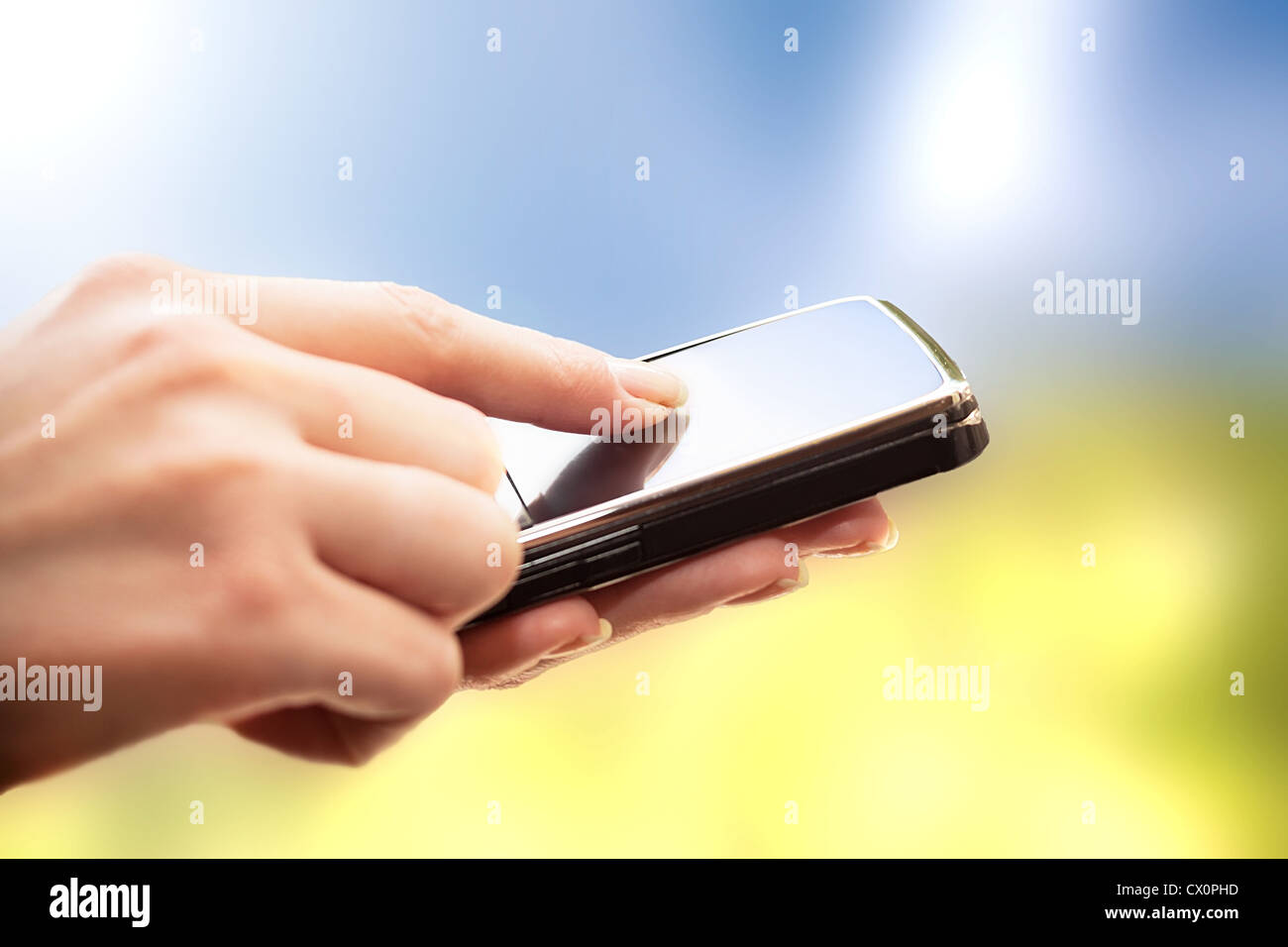 Closeup of female hands using a smart phone. Nature background. - Stock Image