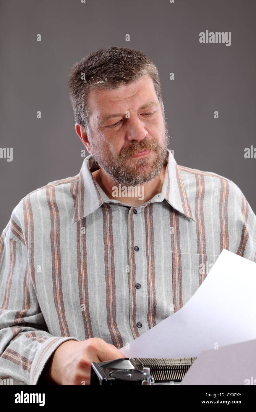 Middle age writer, clerk or journalist looking to paper - Stock Image
