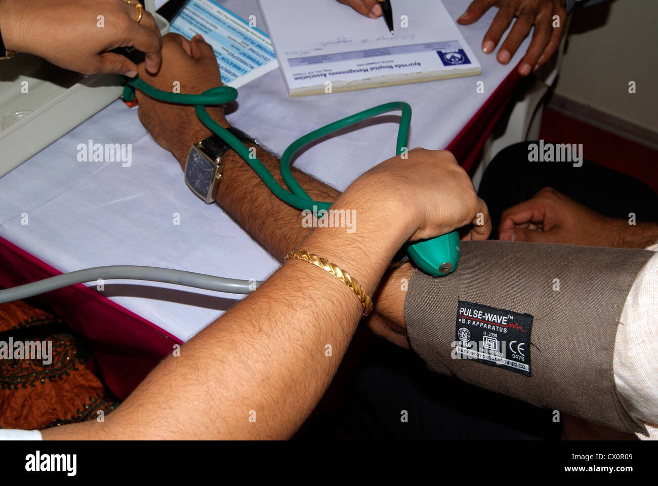 Doctor Checking the Blood Pressure of the Patient using sphygmomanometer Device at Hospital in India - Stock Image