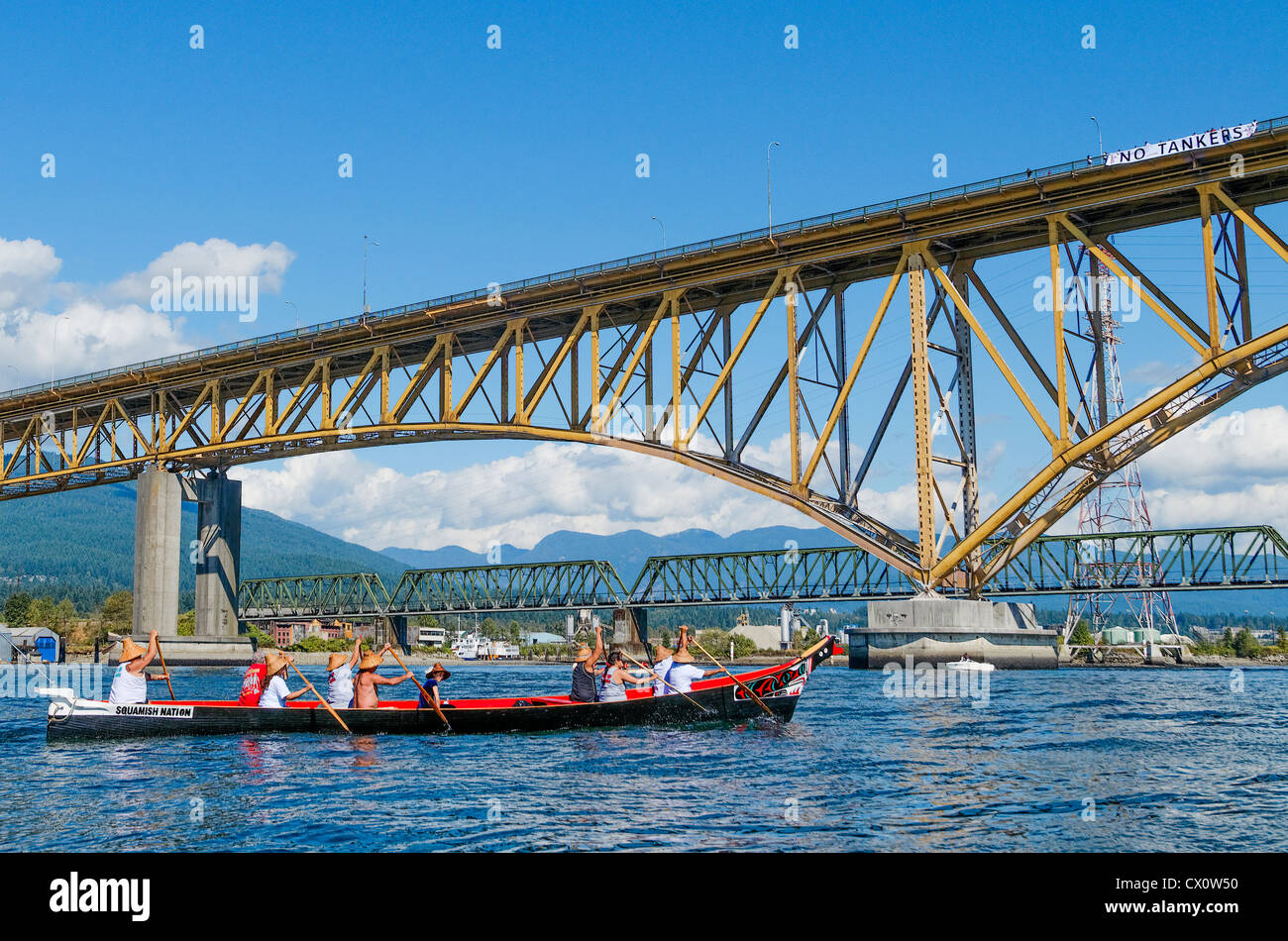 Squamish First Nations canoe approaches Iron Workers Memorial Bridge bearing No Tankers sign - Stock Image
