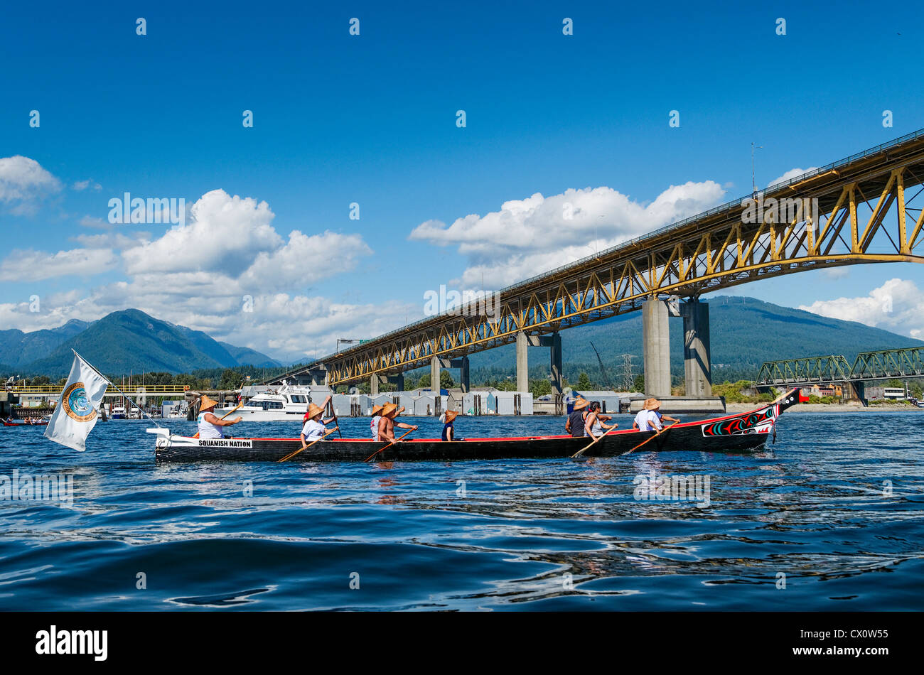 Squamish First Nations canoe approaches Iron Workers Memorial Bridge, Burrard Inlet, Vancouver. - Stock Image