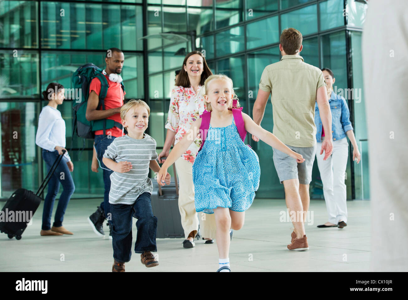 Excited children running on airport concourse - Stock Image