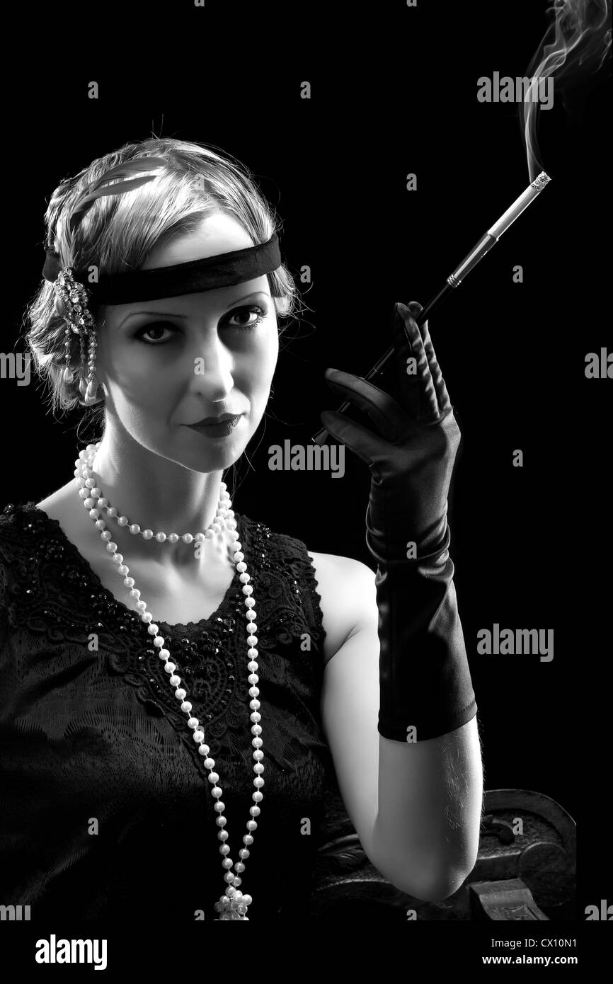 Woman in flapper dress in twenties style smoking a cigarette Stock Photo