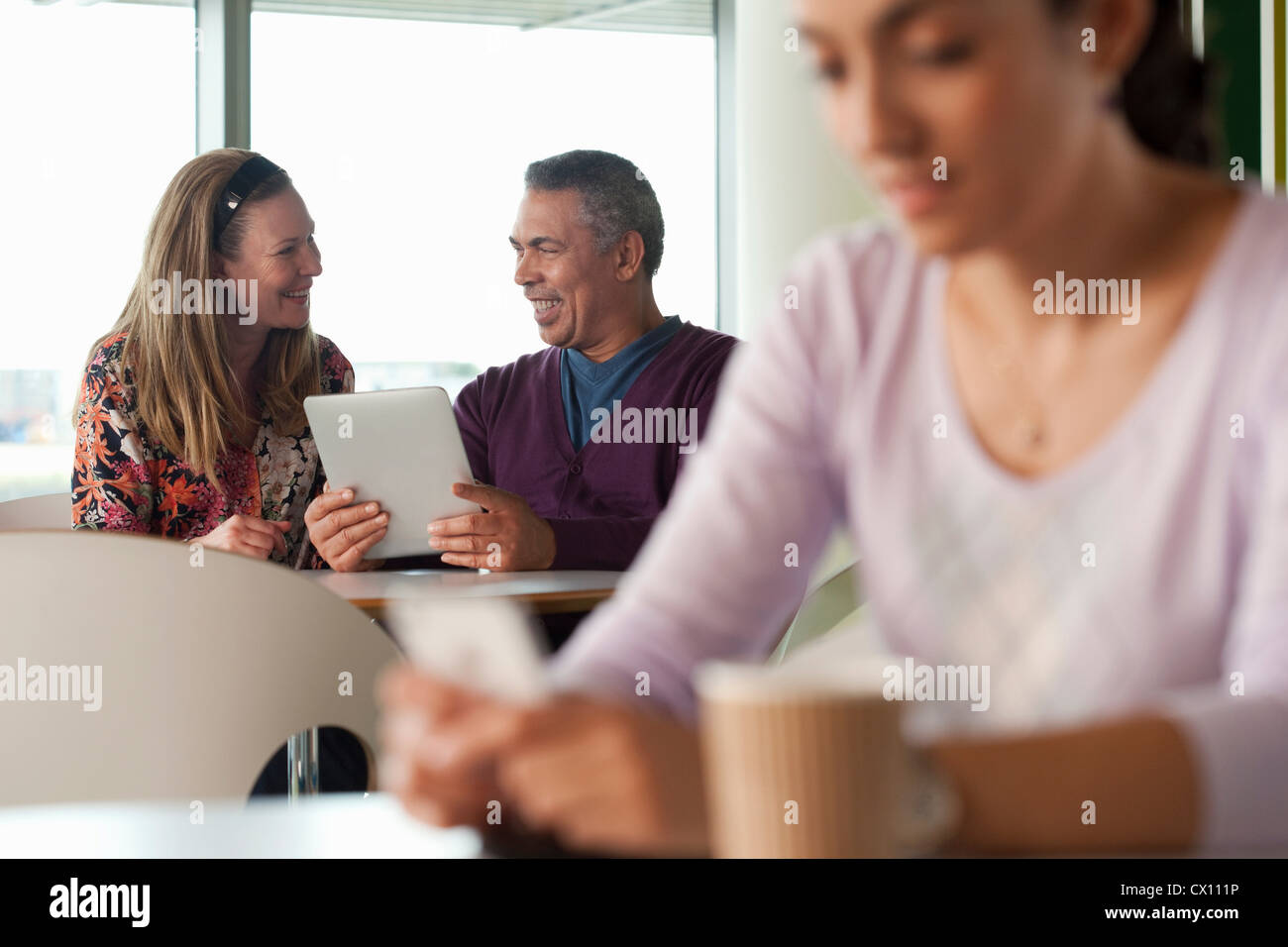 Man using digital tablet, woman texting in foreground - Stock Image