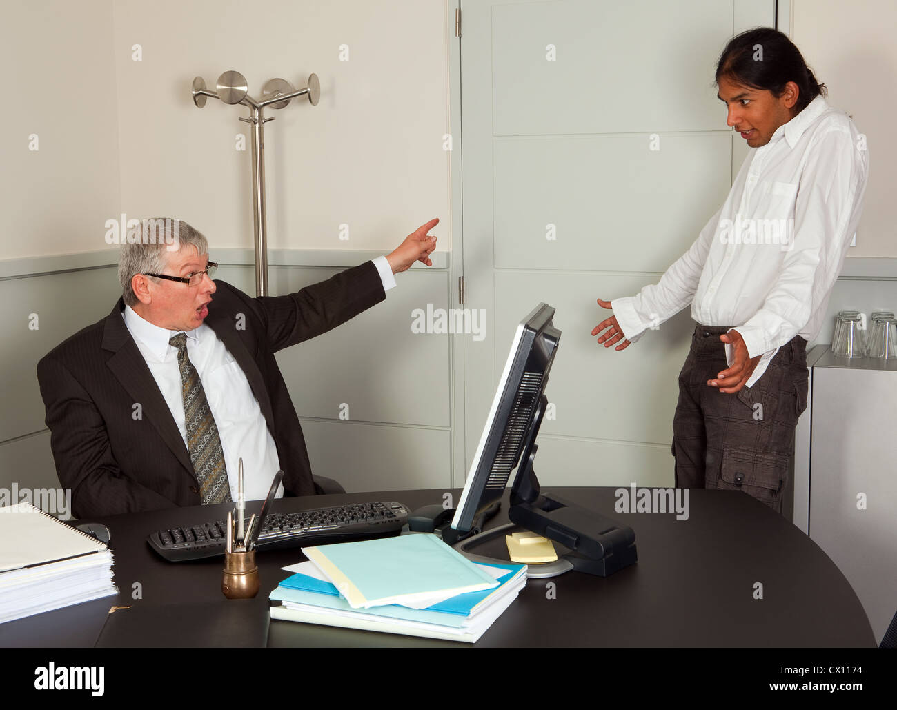 Very angry director firing one of his young employees - Stock Image