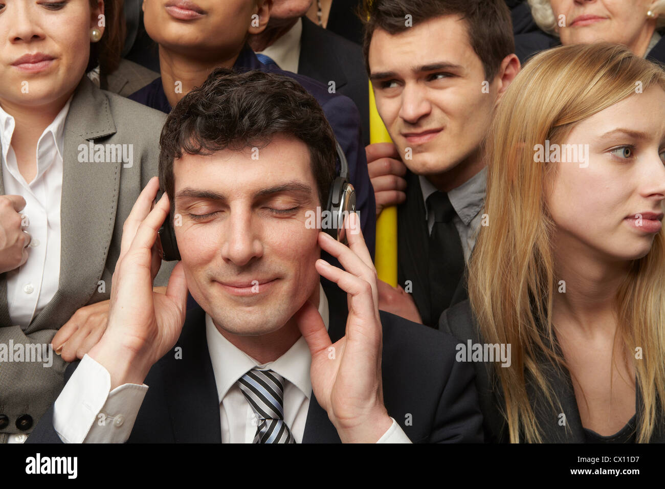 Businesswoman wearing headphones on subway train - Stock Image