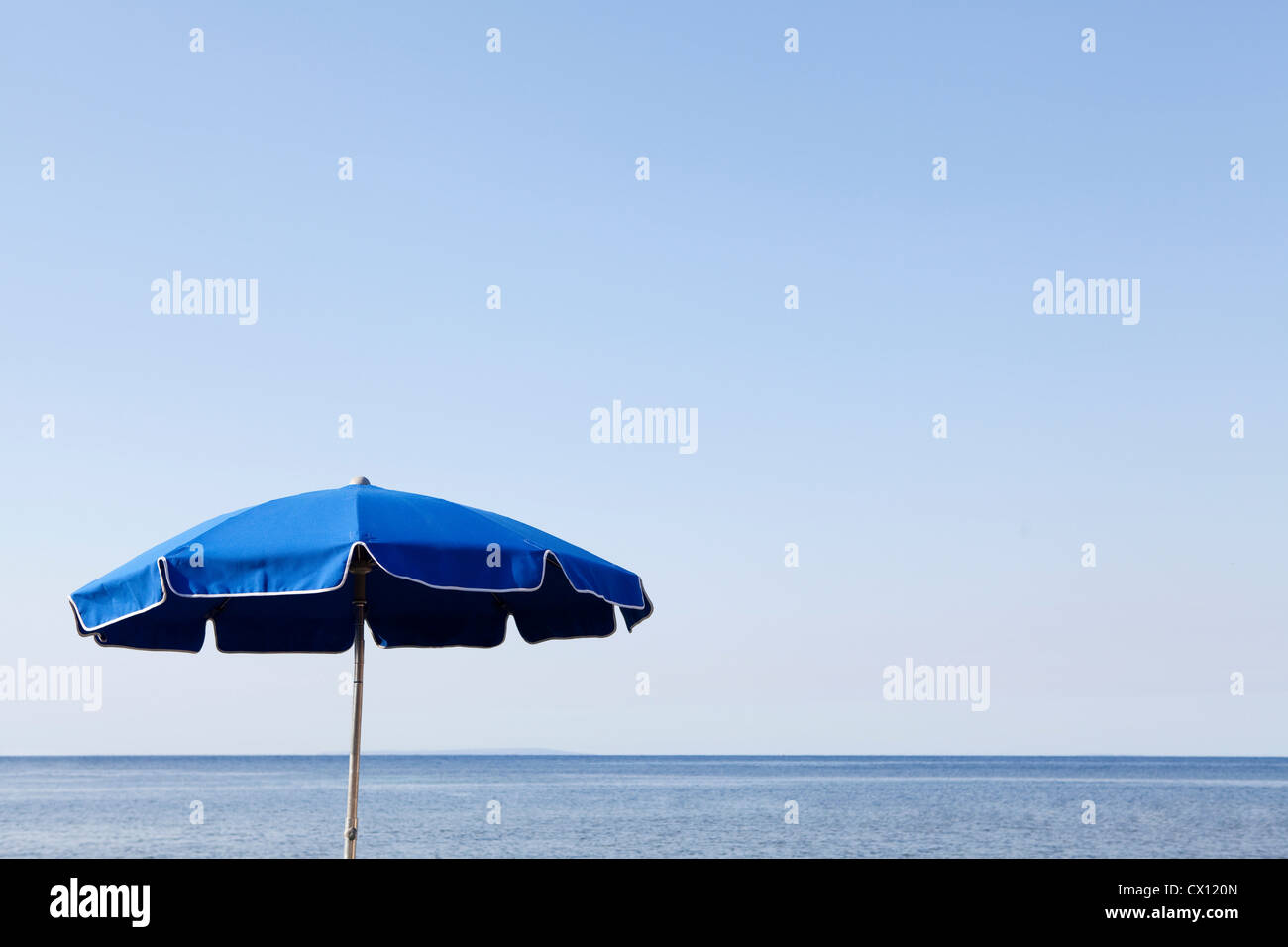 Blue parasol against the sea - Stock Image