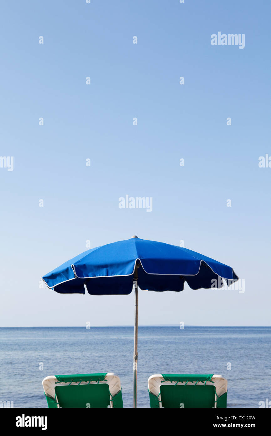 Blue parasol and sun loungers by the sea - Stock Image