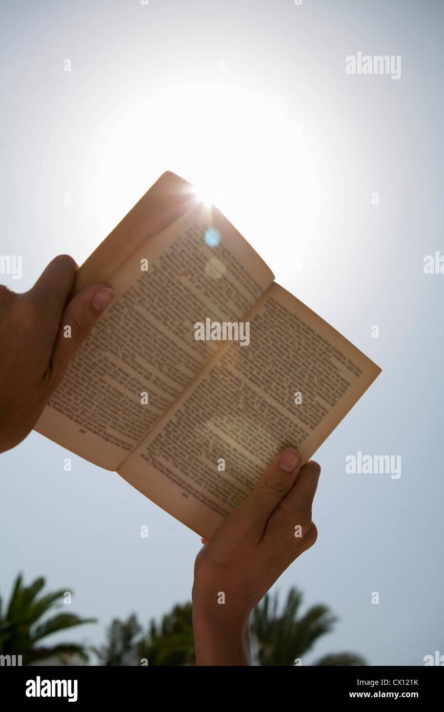 Person holding up book against the sun - Stock Image