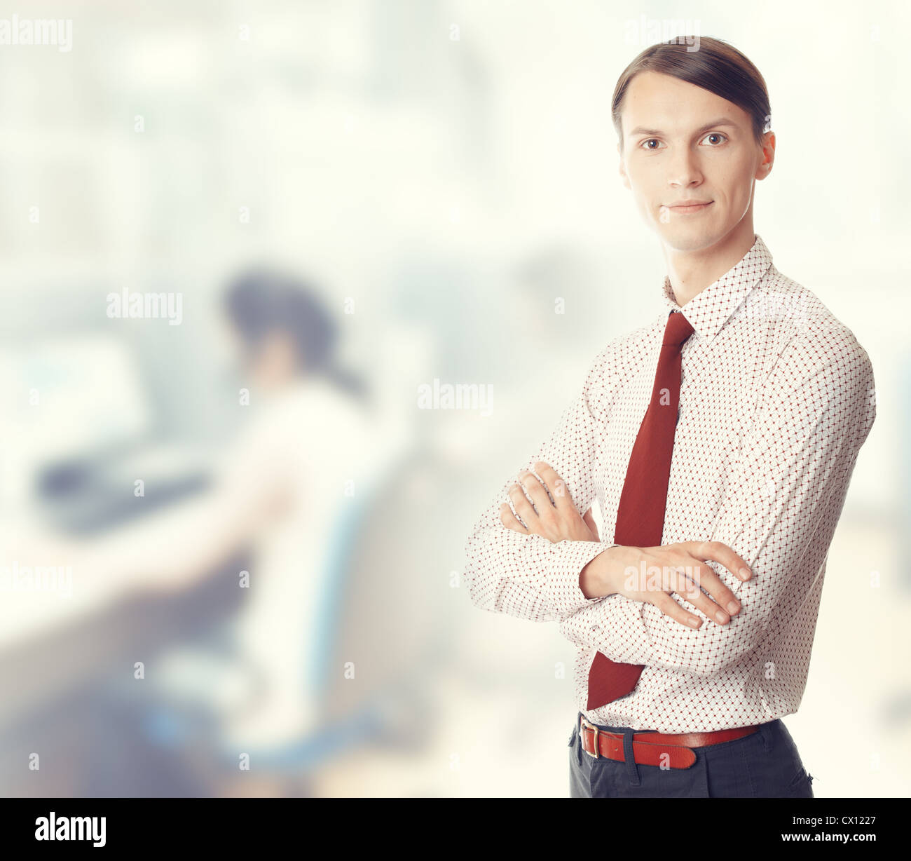 Young businessman stands in defocused office. Color photo - Stock Image