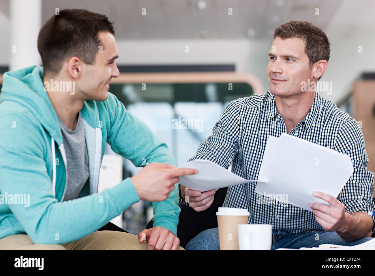 Man giving colleague document - Stock Image