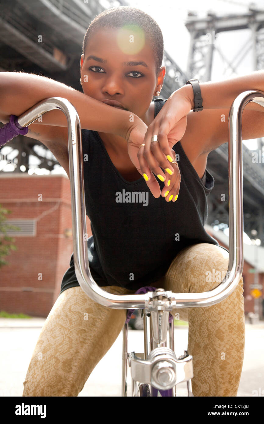 Portrait of a young woman leaning on bicycle handlebars - Stock Image