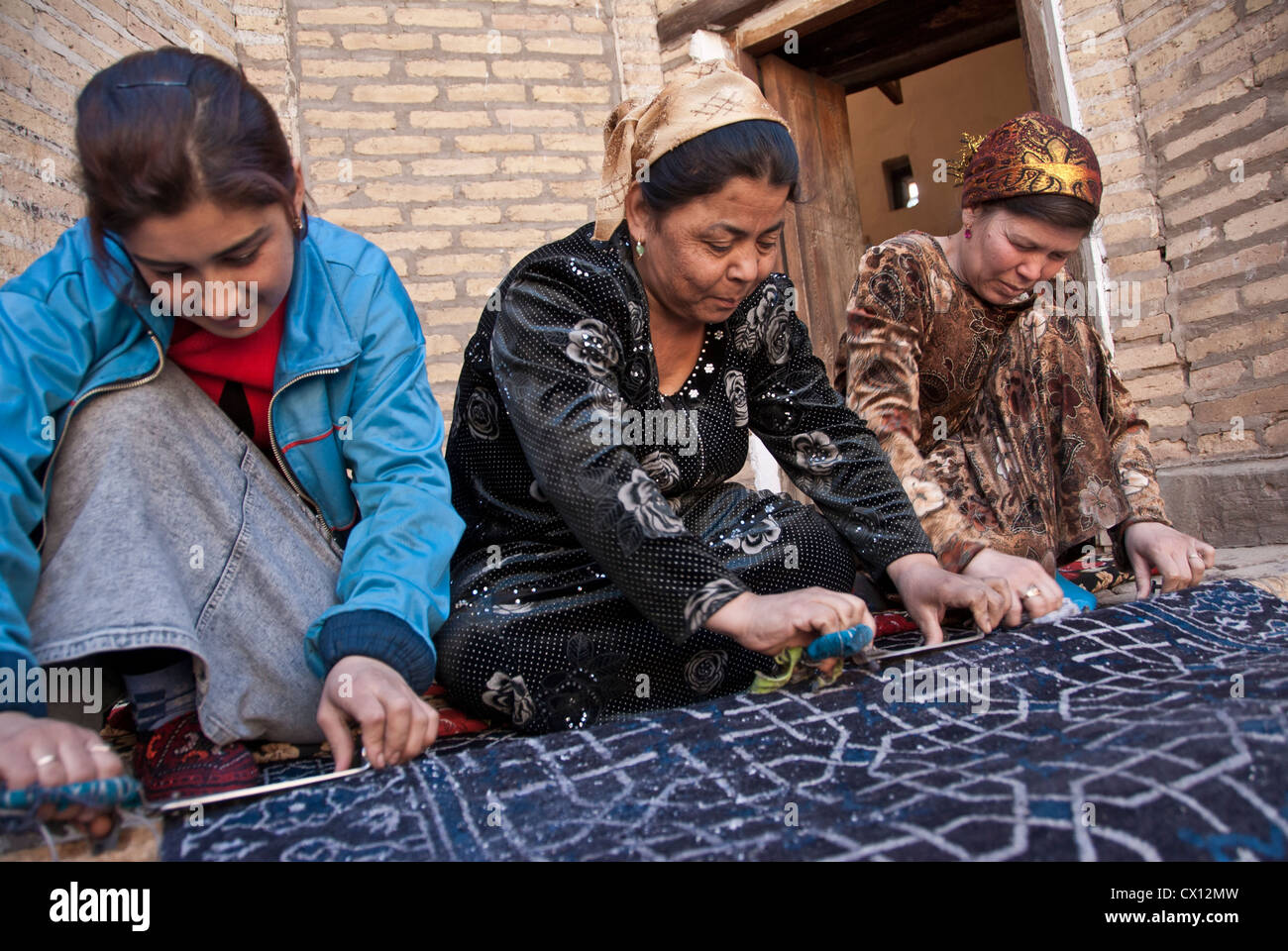 Women weaving traditional carpet, Khiva, Uzbekistan - Stock Image