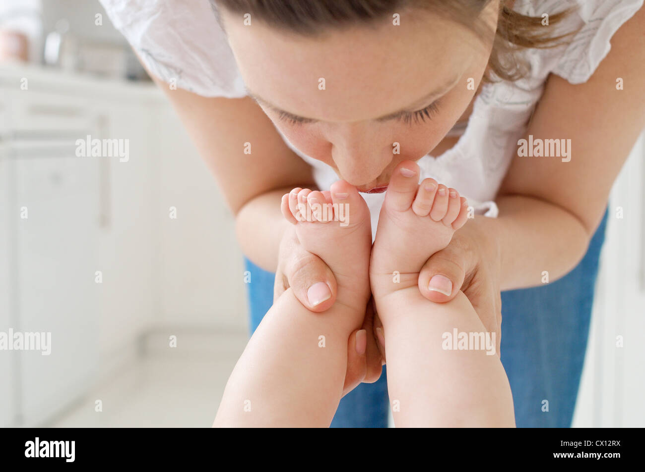 Mother kissing baby's feet Stock Photo