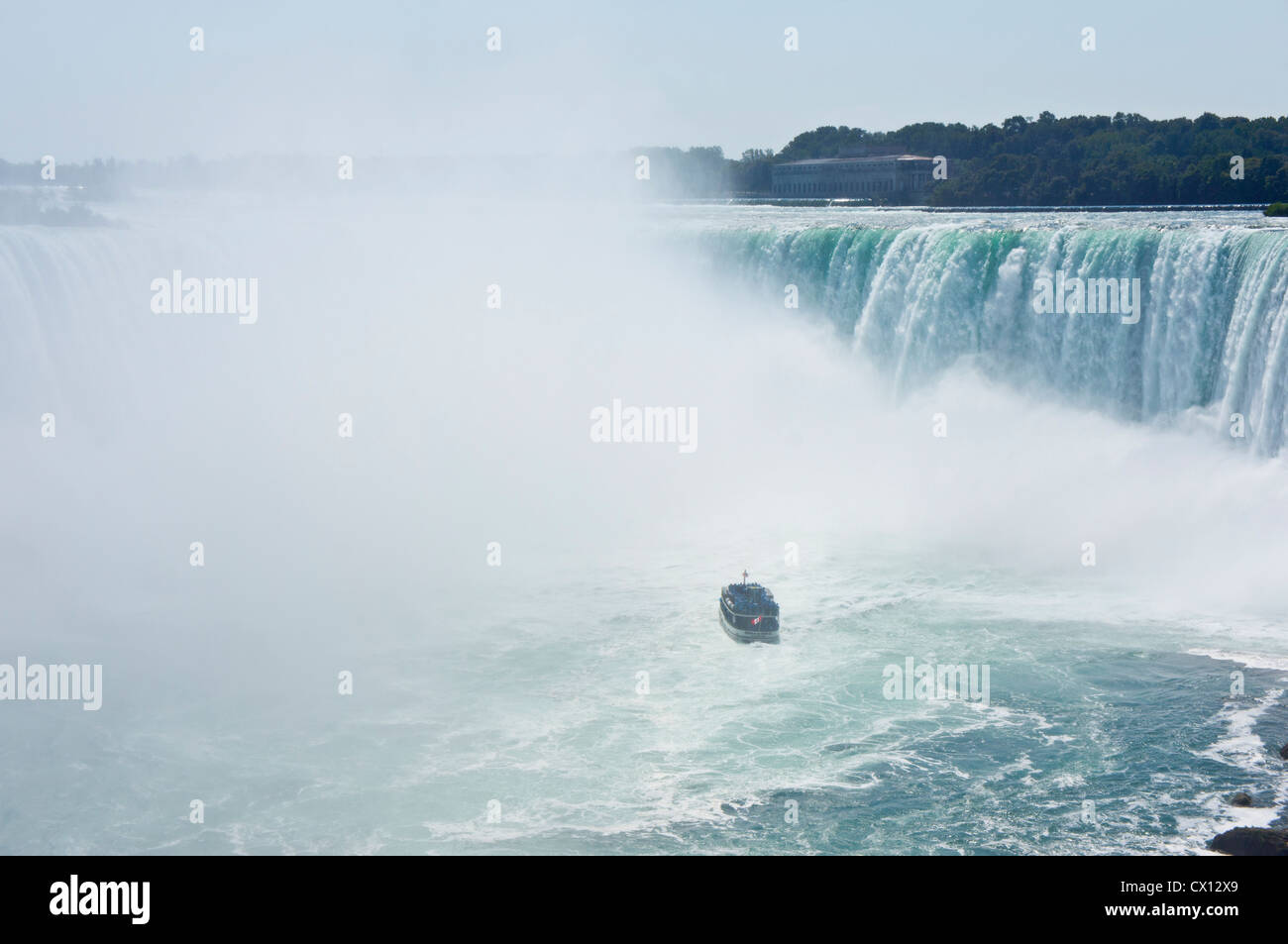 Maid of the Mist flying a Canadian flag at the Horseshoe end of Niagara Falls loaded with tourists dressed in blue - Stock Image