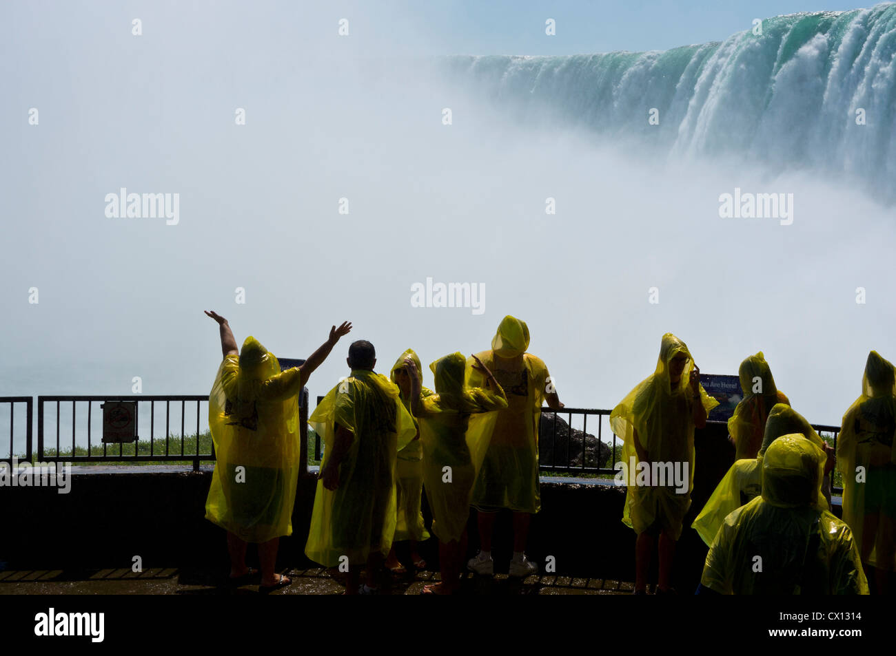 Tourists dressed in yellow waterproof ponchos on the viewing platform at the base of Niagara Falls, Canada. - Stock Image