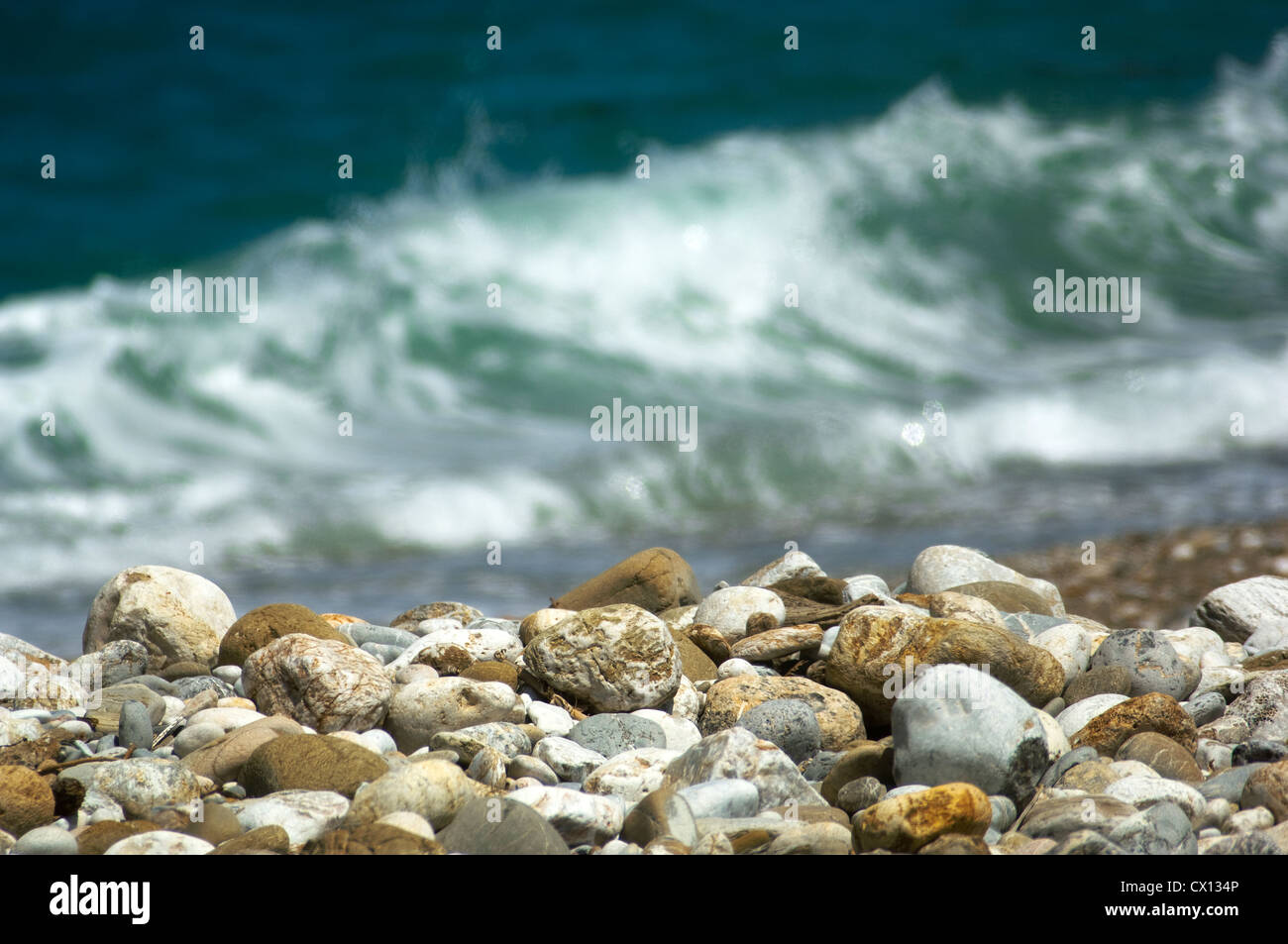 Close-up of a pebble beach with waves in the background - Stock Image